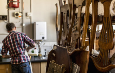 An antique furniture restorer's workshop, chairs piled on a workbench.