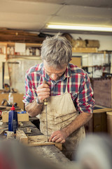 An antique furniture restorer working with a handheld tool on a workbench.