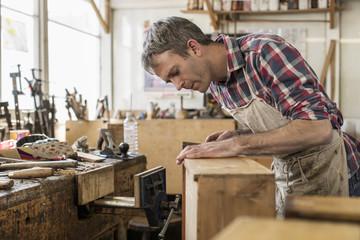 Antique furniture restorer working in workshop