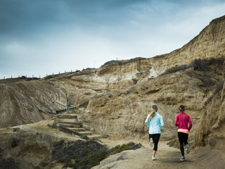 Two women jogging along a quarry trail.