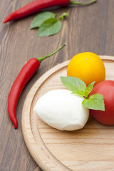 Mozzarella with herbs, fresh vegetables, chilli, on a wooden round board, selective focus