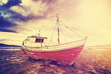 Vintage toned old ship on a beach at sunset.