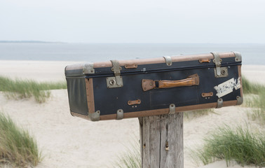 old vintage leather suitcase near the beach