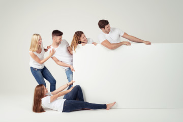 gruppe zieht an einem großen weißen schild