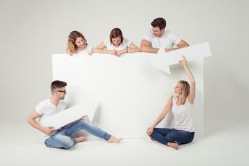junge leute zeigen auf ein weißes plakat