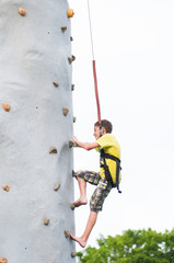 child wearing a harness climbing a rock climbing wall