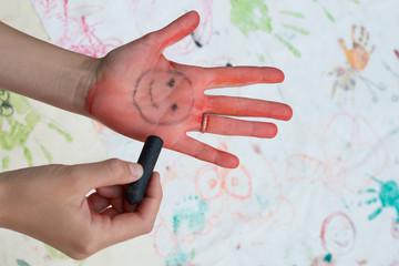手のひらに絵を描いて遊ぶ親子