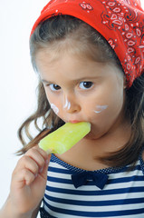 Little girl eating popsicle indoor. Little girl licking a icelolly.