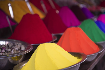 Colorful piles of Indian bindi powder dye at outdoor market in Mysore, India, yellow, green, orange, and red