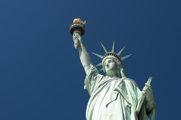 Front view of the Statue of Liberty holding her torch against clear bright blue sky