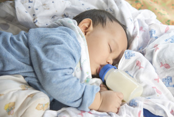 Cute and adorable Asian baby sleeping .Baby drinking milk from the bottle alone on the bed