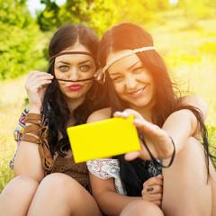 Two boho girls having fun taking a selfie