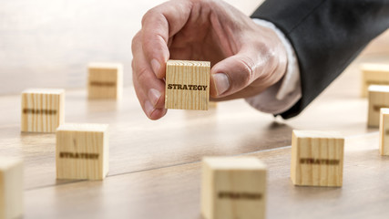 Man Holding Wooden Block with Strategy Text
