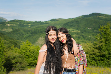 Two beautiful young bohemian sisters hugging outdoors