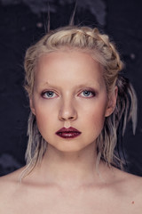 Young beautiful blonde girl with braided in a braid feathers on a black textured background