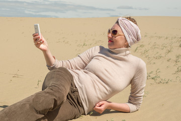 Woman lying on sand and looking at the smartphone