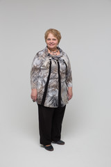 Portrait of an elderly happy woman on a grey background