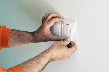 Electricista instalando los interruptores eléctricos durante la reforma de una casa