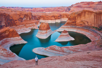 A hiker overlooking Reflection Canyon at the sunset, Glen Canyon National Recreation,  Utah, United States