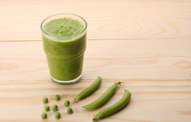 Smoothie with green peas  in a glass and pea pods  on wooden ta