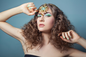 Beautiful fashion model with elegant gold middle eastern headpiece on head looking at camera with serious face and curly hair. on blue background. 