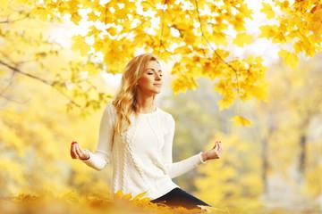 Woman meditating in autumn park