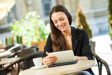 Young woman using digital tablet in a cafe