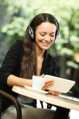 Young woman using tablet and listening music in cafe
