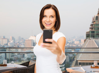 woman taking selfie with smartphone over singapore