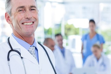 Smiling male doctor looking at camera with arms crossed