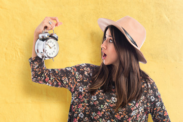 Surprised woman holding vintage clock