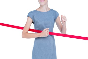 Happy businesswoman cutting red ribbon
