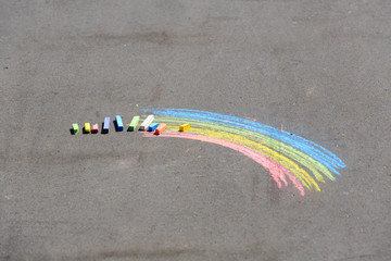 child's drawing of rainbow and chalks on a street