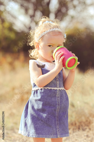 Baby Girl 2 3 Year Old Drinking Water From Plastic Cup Outdoors Wearing Stylish