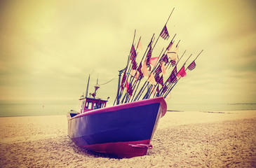 Retro instagram style photo of fishing boat on a beach.