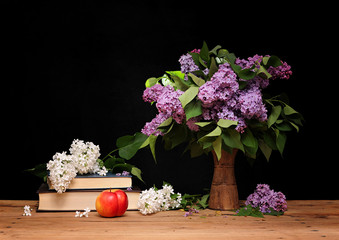 Lilac books and apple on the table