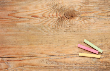Pieces of chalk on a wooden background