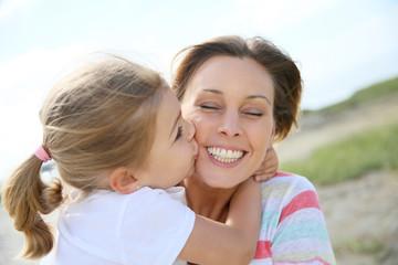 Portrait of cute little girl kissing her mom