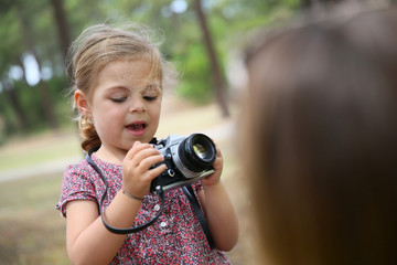 Portrait of little girl taking picture of her parents