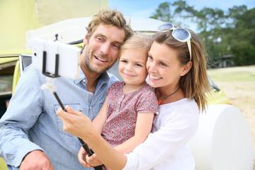 Family standing in front of camper van taking selfie picture