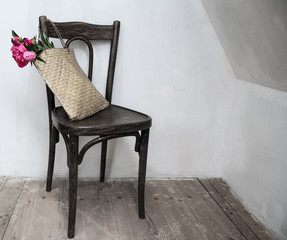 Retro chair in empty room with straw bag and flowers