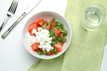 still life of lettuce with fresh tomatoes, parsley, basil, onion, with a handful of granulated cottage cheese in white dish, standing on a green towel and a glass of water and a metal knife and fork