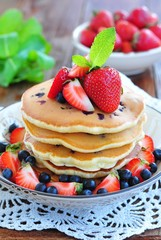 Blueberry Pancake with strawberries and a cup of milk on a wooden table