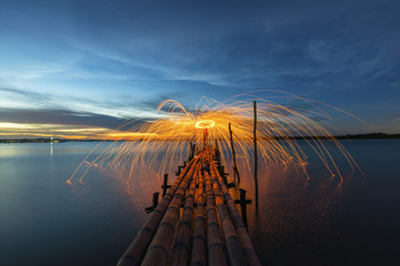 Amazing Fire dancing steel wool coast the sea on bamboo bridge in the twilight