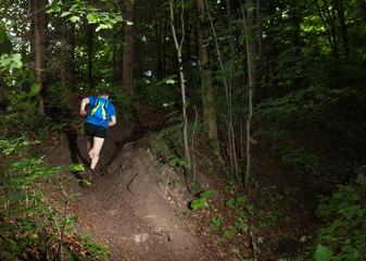 man in blue tshirt with bag running up the hill on the trail in forest