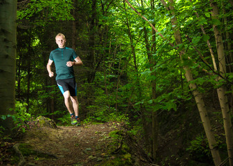 young man trail running on the path in the green forest