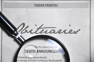 magnifying glass and obituaries advertisement on newspaper