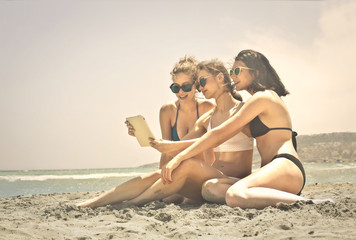 Three girls reading something on a tablet at the beach