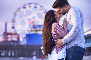 romantic couple kissing in front of santa monica pier