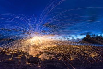 Amazing Fire dancing steel wool coast the sea in the twilight